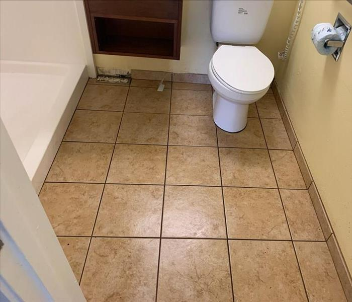 clean bathroom with tan tile floor and white shower and toilet