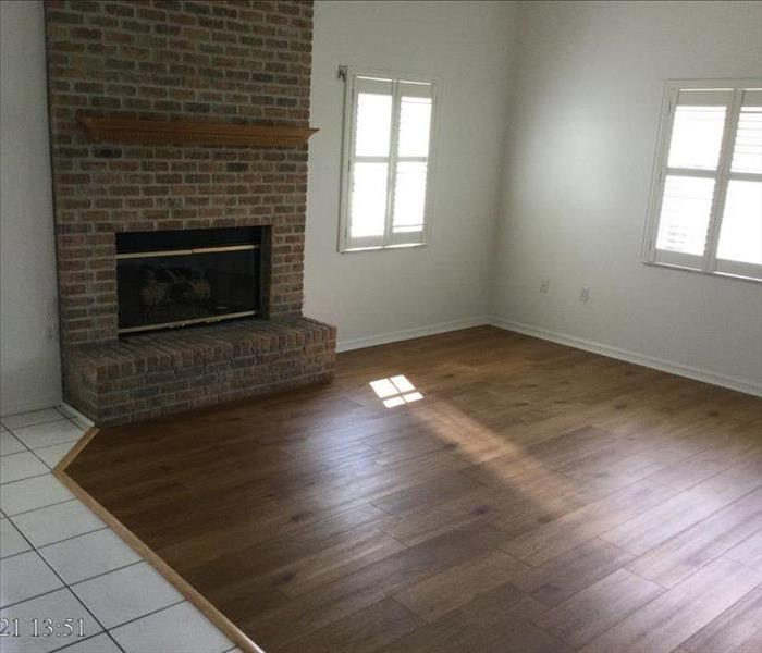 living room with wood flooring, white walls and a brick fireplace