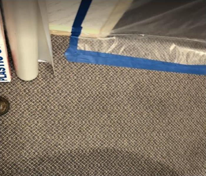 water damaged carpet; plastic sheeting creating a barrier to dry room