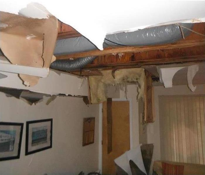 A roof caving in and debris falling after a storm hit this house