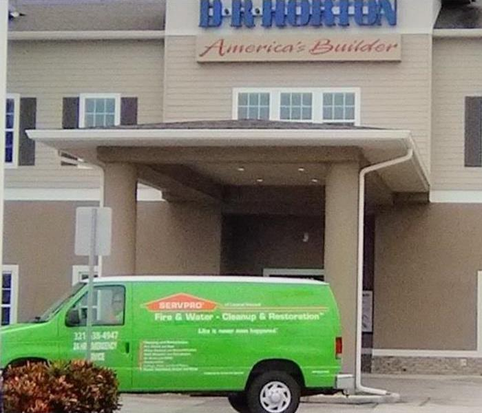 Green SERVPRO van in front of tan building.